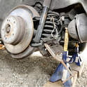With the caliper suspended from the car so the brake hose isn't overextended, a C-clamp and old brake pad can be used to push the pistons back into the caliper.