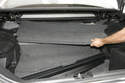 After the trunk blind is removed, the upper trim panel can be shimming out from under the trunk's side panels and set aside.