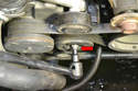 Locate the tensioner and using the E10 Torx driver turn the nut on the wheel (red arrow) counter-clockwise.