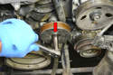 Use a deep socket 15mm and remove the nut and pulley from the tensioner (red arrow).