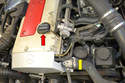 Move to the engine compartment where you will find the oil filter housing (yellow arrow) as well as the oil filler cap (red arrow).