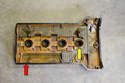 Remove the old gasket around the cover (red arrow) and the four spark plug gaskets (yellow arrow).