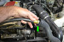 Place your garden hose in the radiator hose (green arrow) and completely flush out the radiator.