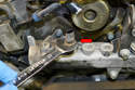 Use a 19mm wrench and remove the sensor from the thermostat housing assembly (red arrow).
