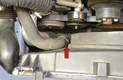Use a screwdriver and unclip the hose on the right side (red arrow).