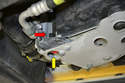 With the tray removed you will see radiator drain plug on the lower left front of the car (yellow arrow).