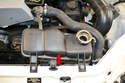Move to the top of the vehicle and remove the coolant over flow tank (red arrow).