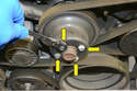 Loosen the four nuts (yellow arrows) on the pulley on the water pump before you loosen and remove the Poly-V belt.