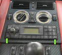 The radio has slots in each lower corner (green arrows) for the removal hooks.