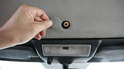 Pop the trim plug out of the headliner to reveal the manual latch screw.