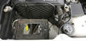 Inspect the fender cavity below the battery tray for lost tools and rodent nests.