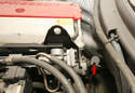 Use a small screwdriver to depress the filler cap's retaining clip (red arrow), then remove the cap.