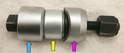 The new bushing (yellow arrow) is centered in the suspension arm using a sleeve that abuts the outer shell but is larger than the arm's hole (blue arrow).