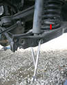 Before unbolting the shock absorber from the lower control arm, compress the coil spring using the special tool (arrow).