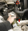 For an in-car fluid change, clean the area around the plug (arrow) prior to removing it.