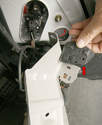 Unbolting the bracket with a T27 Torx bit allows the switch (arrow) to be slid out of its mounting slots.