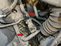 Use a flathead screwdriver and remove the clamps and two hoses connected to the auxiliary pump (red arrows).