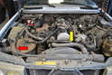 There are two hoses visible from the top of the engine: the radiator to expansion tank overflow hose (red arrow) and the radiator to thermostat housing hose (yellow arrow).