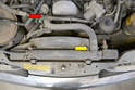 To replace the top hose use a flathead screwdriver and remove the clamps where the hose joins the radiator (yellow arrow) and the thermostat housing (red arrow).