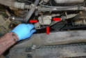 Use a 10mm socket and remove the three bolts holding the front of the thermostat housing in place (red arrows).