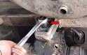 With the weight on the jack, use a 22mm socket and remove the two bolts (red arrow).