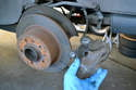 To begin, you will need to remove the brake caliper and safely hang it out of the way.
