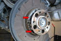Use a long pick and slide it through an opening in the wheel hub and pry off the retracting spring from the two shoes by the expander (red arrows).