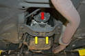 The transmission mount mounts by a single 19mm nut to the tail of the transmission (red arrow) and two 13mm bolts to the cross-member (yellow arrow).
