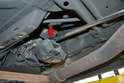 Use a 19mm wrench (preferable geared because of the tight working conditions) and remove the single nut holding the mount to the transmission (red arrow).