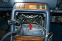 There is a bulb mounted in the rear of the console opening (red arrow) that you will need to carefully reach in and remove.