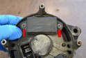 Use a Philips head screwdriver and remove the two screws (red arrows) holding the regulator in place.