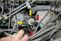 Disconnect the vacuum lines to the transmission switch over valve (red arrows) and then use a 5mm Allen to remove the two bolts (yellow arrows) from the switch over valve and set it off to the side.