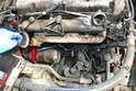 There are aftermarket kits that eliminate the trap and attach directly to the out port of the exhaust manifold (red arrow) and to the turbo but check with the regulations in your area before making this modification.