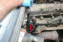 Use a 13mm wrench and remove the bolt holding the transmission tube to the rear of the intake manifold (red arrow).