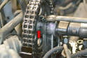 With the rockers removed use a 27mm wrench and turn the motor clockwise by the nut on the crankshaft dampener until the marks line up at Top Dead Center on the camshaft chain sprocket and tower housing (red arrow).