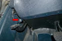 Use a Philips head screwdriver and remove the large plastic screw (red arrow) by the parking brake.