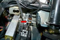 The switch is mounted to a bracket in front of the brake pedal arm (red arrow).