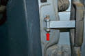 Use a punch and a small hammer and tap the retaining pin out from the mount on the chassis (red arrow).