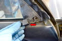 With the tab pushed in, you can pull the plastic piece off the metal arm back towards the rear of the door (red arrow).
