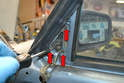 Use a Philips head screwdriver and remove the three screws holding the mirror to the door (red arrows).