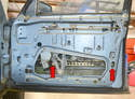 With the door panel removed raise or lower the window until you can access the two 10mm bolts that hold the window glass to the regulator (red arrows).