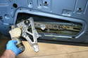 Lower the motor and compress the arms on the mechanism and remove it from the opening in the lower door.