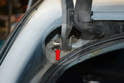 Use a flathead screwdriver to release the clip and then push the pin back out from the hinge on the hatch (red arrow).