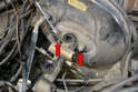 Use a 13mm wrench and remove the two nuts holding the master to the booster (red arrows).
