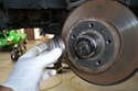 Use a large set of pliers or a punch and remove the grease cap from the end of the spindle.