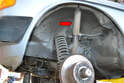 To get better access to the inner bolt slightly compress the shock from the top and tilt it outward (red arrow).
