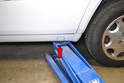 Just in front of the rear wheels are indentations in the rocker panels (red arrow, one on each side).