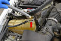 Use a garden hose and run water through the reservoir until water comes out of the engine and hoses clear (red arrow).