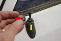 Working on the rear exterior of the vehicle use an adjustable wrench and un-screw the two nuts (red and yellow arrows) on the exterior of the antenna mast.