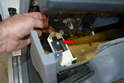 Lower the dash and remove the parking brake cable from the handle by turning the cable so the